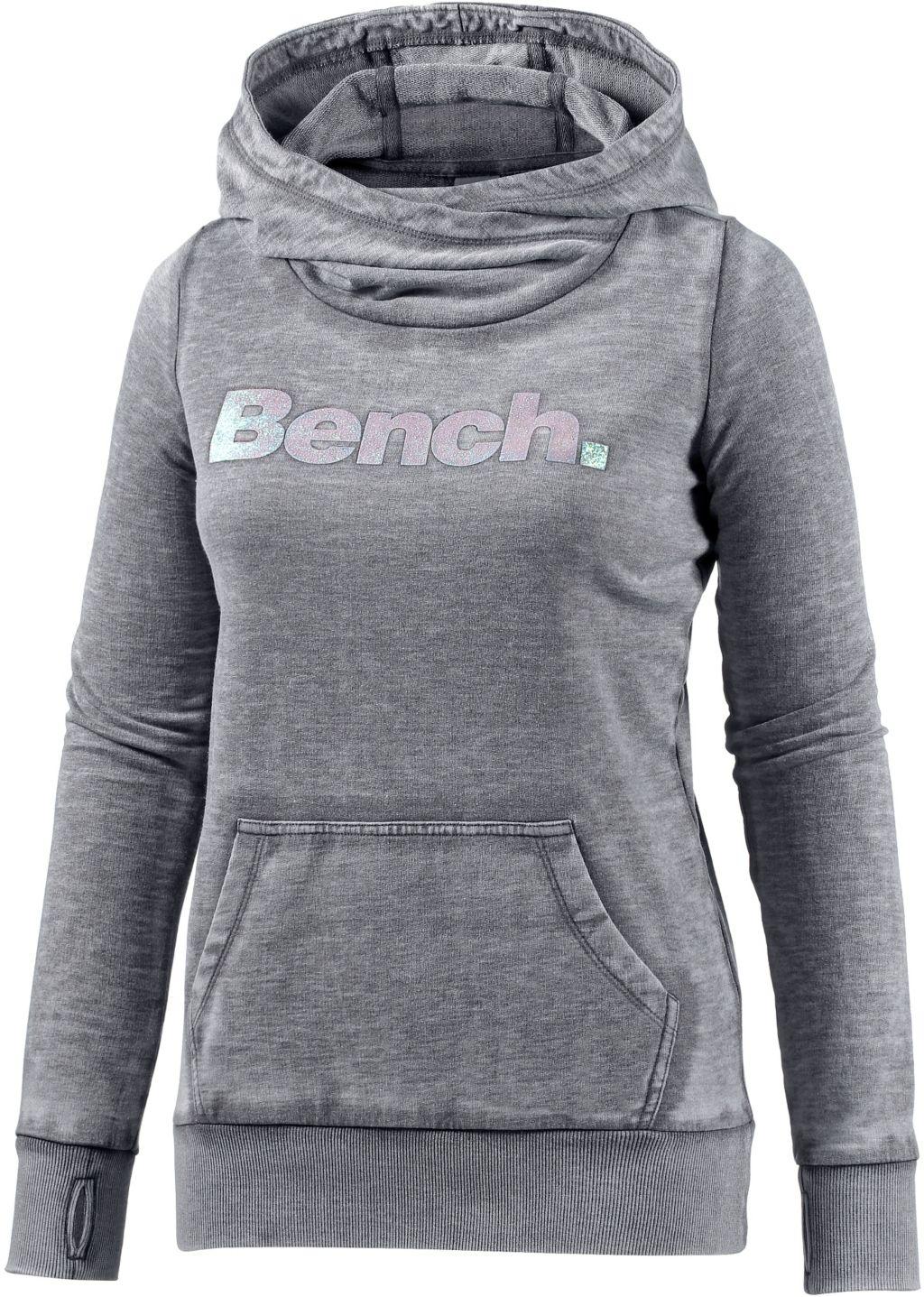 Artikel klicken und genauer betrachten! - Bench Kapuzen Sweatshirt mit glitzerndem Markenschriftzug auf der Front und hohem, überkreuztem Kragen; Kängurutasche, Ärmel mit Daumenschlupf; Rippbündchen an Ärmeln und Saum; Material 65% Polyester, 35% Baumwolle.   im Online Shop kaufen